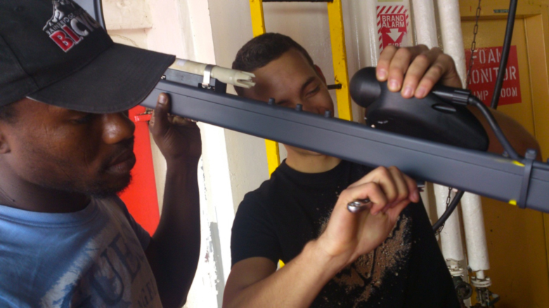 Engineering interns, Sinekhaya Bilana and JP Smit work on sensors of the Wave Glider before deployment from the polar ship SA Agulhas II.